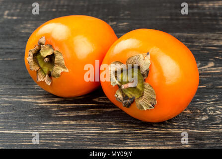 Due frutti maturi cachi su sfondo di legno closeup Foto Stock