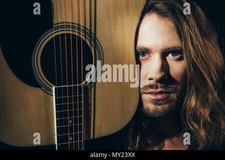 ... Close-up ritratto di bello barbuto dai capelli lunghi uomo con chitarra  e guardando la 532a986f24b6