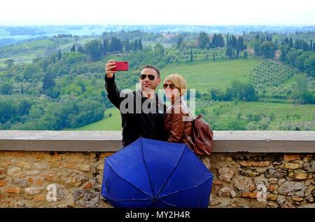 I turisti tenendo selfie a san gimignano, Toscana, Italia Foto Stock
