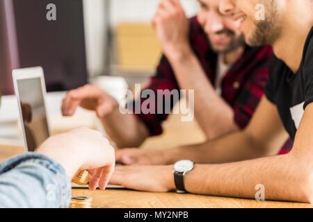 Gruppo di happy amici seduti insieme davanti a un computer portatile. Concentrarsi sulle mani dell'uomo cryptocurrency holding. Foto Stock