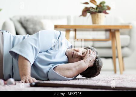 Senior donna con un mal di testa dopo la caduta verso il basso a casa