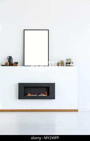 Mockup del poster vuoto nero sopra il camino in semplice bianco living room interior. Foto reale con un posto per la vostra scheda grafica Foto Stock