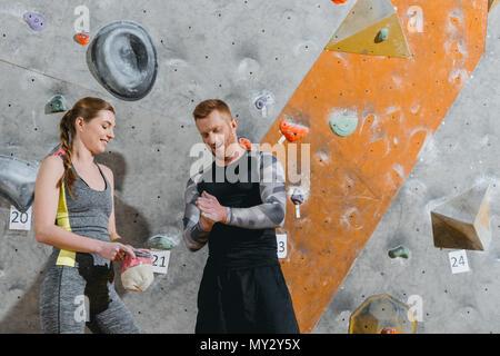 A mezza lunghezza shot del giovane uomo in abbigliamento sportivo applicare talco alle mani e una donna in possesso di un sacco di polvere Foto Stock