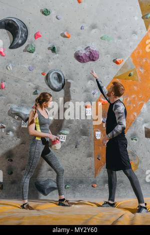 A tutta lunghezza shot del giovane uomo che puntano a presa sulla parete di arrampicata e la donna accanto a lui lo sta guardando Foto Stock