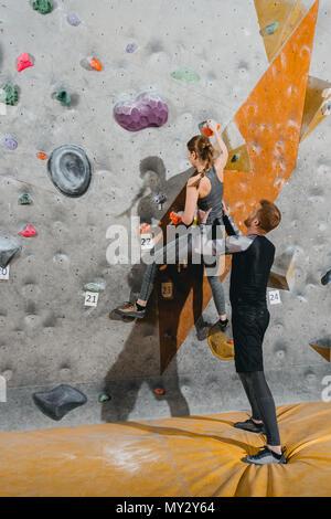 A tutta lunghezza shot della giovane donna salendo una parete con impugnature con uomo il suo supporto da dietro Foto Stock