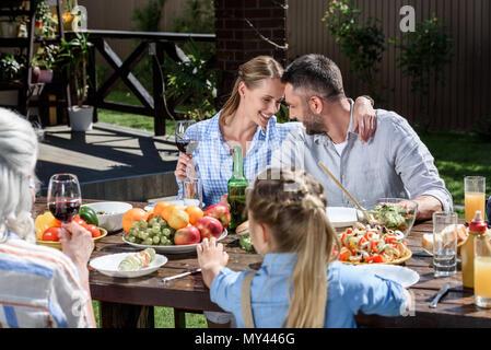 Ritratto di uomo sorridente e la donna seduta a tavola con la famiglia nelle vicinanze Foto Stock