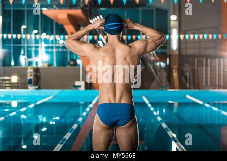 ... Vista posteriore del nuotatore muscolare in cuffia per la piscina e gli  occhiali in piedi alla 2b98839c7eaf
