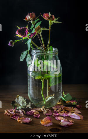 Natura morta con rose appassite in vaso di vetro sul tavolo di legno
