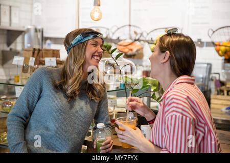 Due giovani amici di sesso femminile ridere insieme al cafe Foto Stock