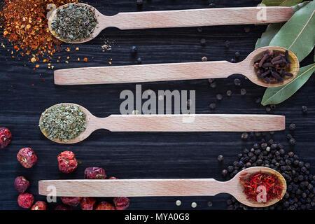 Quattro cucchiai di legno con varie spezie scuro su sfondo di legno Foto Stock