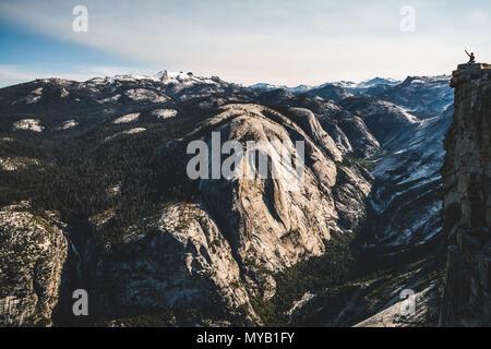 Un minuscolo, escursionista solitario sulla sommità di Half Dome nel Parco Nazionale di Yosemite.