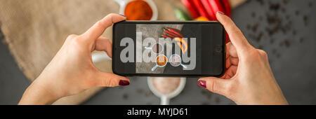 Vista superiore della donna in possesso di un telefono e di scattare una foto di un alimento sano per il suo blog culinario Foto Stock