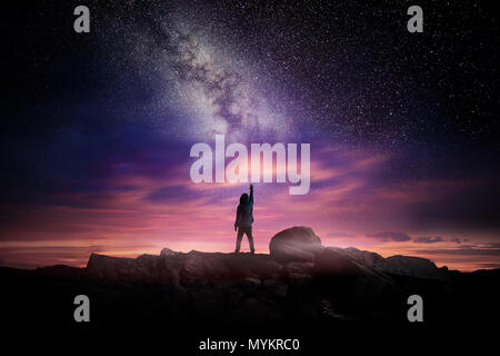 Tempo di notte lunga esposizione fotografia paesaggistica. Un uomo in piedi in un alto luogo portandosi fino a meraviglia per la Via Lattea, foto composite. Foto Stock