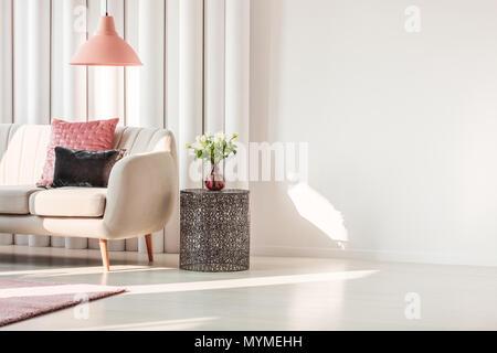 Semplice soggiorno interno con rosa e grigio cuscini sui divani beige e rose sul tavolo in metallo Foto Stock
