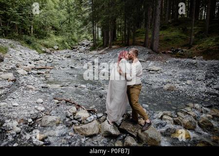 Bella giovani sposi kissing mentre in piedi sulle rocce in rapida fiume di montagna, le Alpi