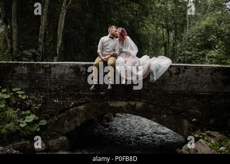 Bella giovani sposi kissing mentre è seduto sul ponte sopra il fiume di montagna nelle Alpi