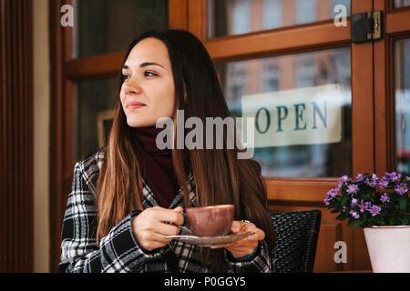Giovane bella ragazza beve caffè o cioccolata calda in una street cafe Foto Stock