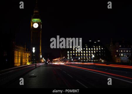 Casa del Parlamento e dal Big Ben di notte e sentieri di luce sul Westminster Bridge da veicoli di passaggio. Foto Stock