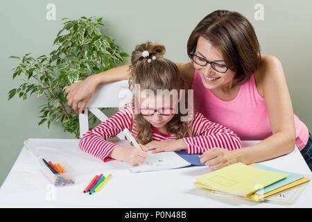 Amorevole Madre aiutare la propria figlia scuola elementare allievo scrivere nel suo notebook, a casa a tavola. Si torna a scuola concetto. Foto Stock