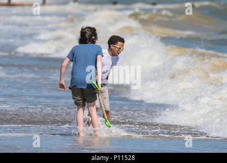 Coppia di ragazzi su una spiaggia in riva al mare a giocare come le onde si rompono vicino in Inghilterra, Regno Unito. I ragazzi guardano a essere di origini etniche diverse. Foto Stock