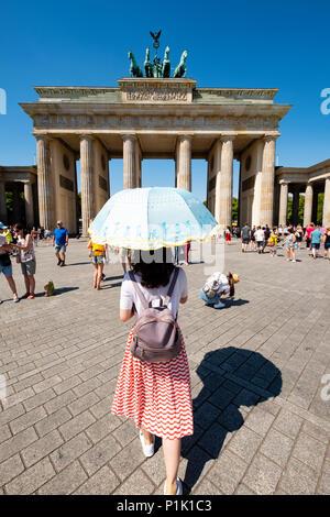 Turisti cinesi con sun parasol nella parte anteriore della porta di Brandeburgo a Berlino, Germania Foto Stock