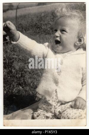 La REPUBBLICA SOCIALISTA CECOSLOVACCA - Circa ottanta: Vintage mostra fotografica di baby boy all'esterno. Antique Black & White photo.