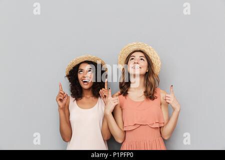 Ritratto di due felici donne multietnica e caucasica african american ragazze indossando cappelli di paglia sorridere mentre denti rivolti verso l'alto a copyspace è Foto Stock