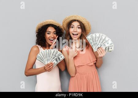 Ritratto di due multietnica di successo le donne e caucasica african american ragazze indossando cappelli di paglia tenendo gli appassionati di denaro dollaro 100 banconote isola Foto Stock