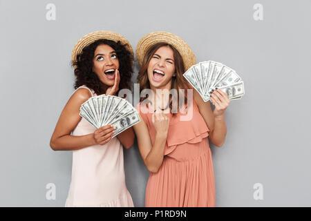 Immagine di due eccitati donne multietnica e caucasica african american ragazze che indossano vestiti estivi tenendo un sacco di soldi le fatture del dollaro isolate su Foto Stock