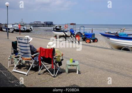 Coppia senior in seduta sdraio in spiaggia, cromer Promenade, North Norfolk, Inghilterra Foto Stock