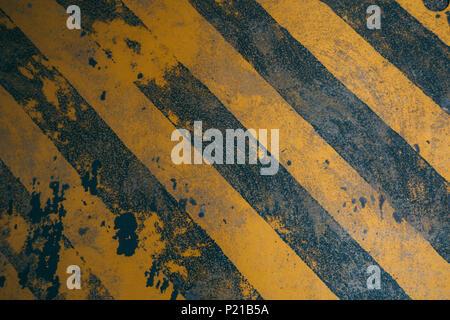 Sporco diagonale giallo di avvertimento sullo sfondo delle linee per costruzione di pericolo Foto Stock
