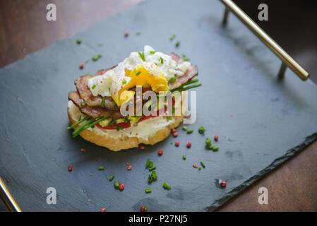Delizioso sandwich con uovo in camicia, avocado e pancetta su un vassoio di ardesia (messa a fuoco selettiva) Foto Stock