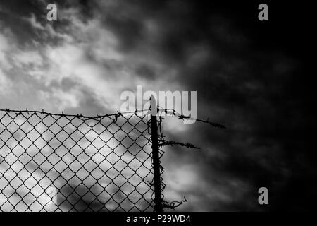 Un recinto rotto su un cielo scuro. Filo spinato sulla parte superiore. In bianco e nero girato. Colpo simbolico: evasione, la prigione, la speranza, la guerra. Foto Stock