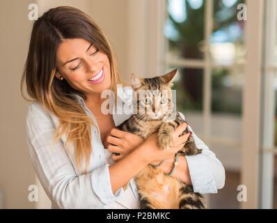 Giovane bella donna sorridente e coccole Gatto con amore a casa. Foto Stock