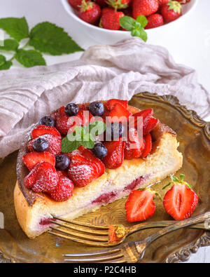 Cheesecake fatta di ricotta e fragole fresche su un piatto e decorate con fragole fresche e mirtilli, vista dall'alto Foto Stock