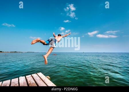 Ragazzo immersioni subacquee da un molo, South Beach, Burgtiefe, Fehmarn island, costa baltica, Schleswig-Holstein, Germania Foto Stock