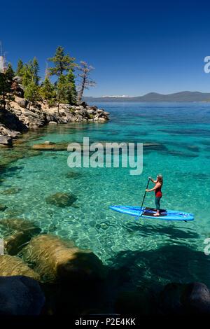 Donna stand up paddle boarding sulle acque blu cristalline del lago Tahoe in Incline Village, Nevada, Nord America. Foto Stock