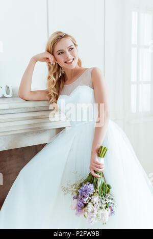 Giovane e bella sposa in abito da sposa appoggiata sul camino Foto Stock