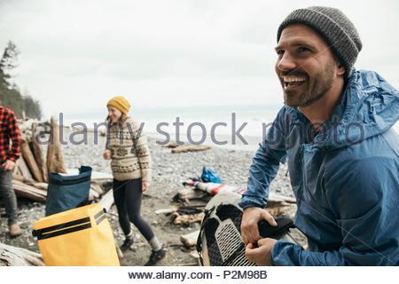 Uomo sorridente godendo weekend Surf vacanza con gli amici sulla spiaggia di robusti Foto Stock