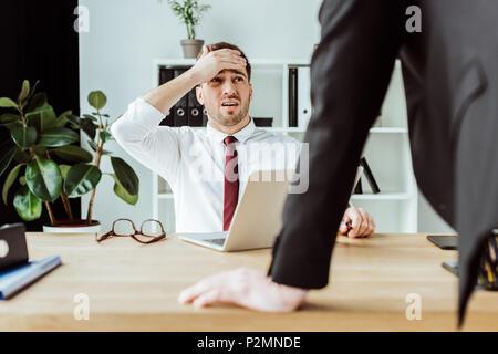Spaventata uomo d affari con computer portatile guardando arrabbiato boss in ufficio Foto Stock