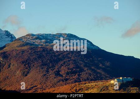Un costoso hotel è costruito su una collina che guarda verso il basso su Ushuaia, Argentina. In ritardo la luce del sole illumina il bosco d'autunno. Foto Stock