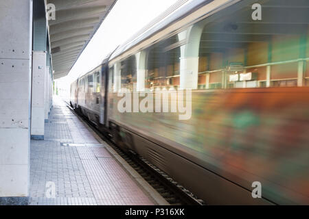 Treno elettrico passante, movimento sfocati in corrispondenza di una stazione ferroviaria in Grecia. Foto Stock