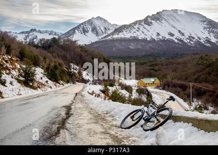 Una mountainbike è appoggiato accanto alla strada tra il Ghiacciaio Marziale e la città di Ushuaia. La neve ha reso la discesa più pericolosa. Foto Stock