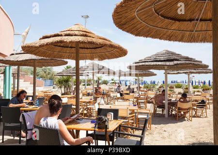 Blue Moon Pizzeria, Blue Moon Beach, Lido di Venezia, Venezia, Veneto, Italia. Persone mangiare sotto gli ombrelloni di paglia in tarda primavera, attrazione turistica Foto Stock