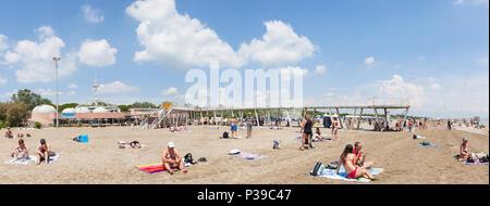 Panorama di Blue Moon Beach, Lido di Venezia, Venezia, Veneto, Italia in tarda primavera con il molo e ristoranti, persone nuotare e prendere il sole Foto Stock