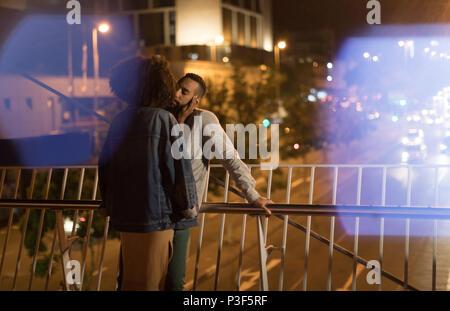 Paio di baciare ogni altro mentre è in piedi vicino alla ringhiera di protezione Foto Stock