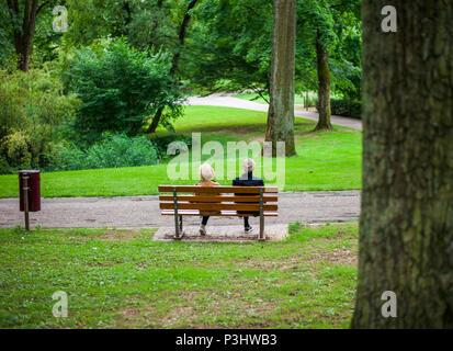 Un vecchio paio di seduta sul banco in un parco pubblico, Lussemburgo Foto Stock
