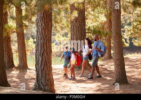 Famiglia su escursioni avventura attraverso boschi dal lago