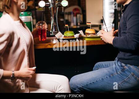 Un gruppo di giovani seduti ad un cafe, parlando e godendo Foto Stock