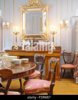 Grande ed antico specchio dorato sopra ornato caminetto in soggiorno con carta da parati - Specchio dorato antico ...